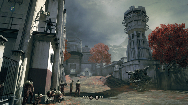 A labor camp yard, overlooked by a Nazi guard and a giant mech.