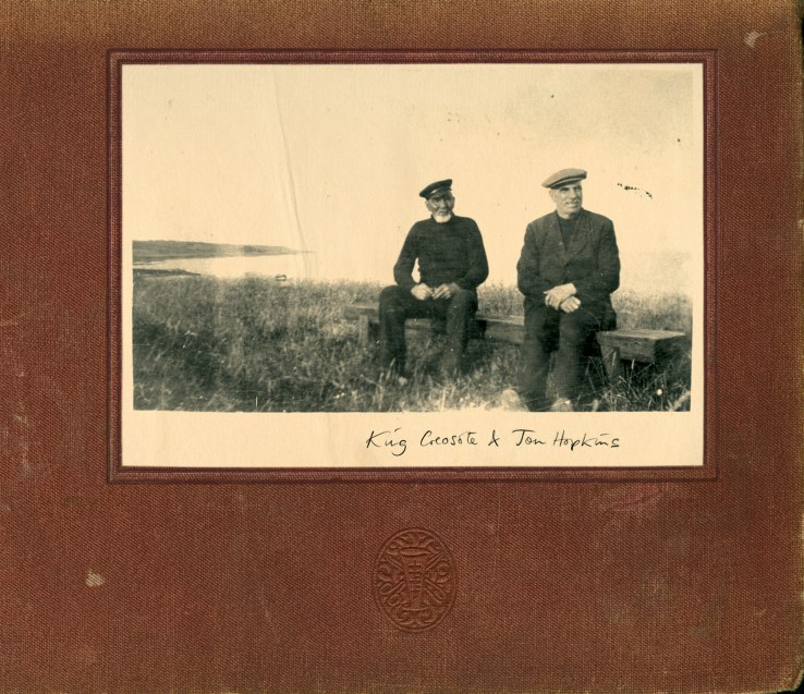 The album cover of Diamond Mine by King Crosote and Jon Hopkins. It depicts 2 older men sitting on a bench in a grassy field next to the coast. The picture is worn and is surrounded by a brown scrapbook frame