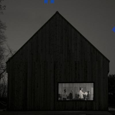 The cover of the National's Sleep Well Beast. A black and white photo of a large barnhouse, with one window. Where a few people stand