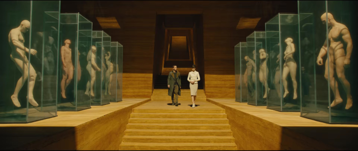 K (Ryan Gosling) and Luv (Sylvia Hoeks) walk down a golden wooden stairwell. In glass cases on both sides of the frame are mannequin like models of people.