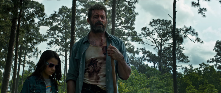 Logan (Hugh Jackman) and Laura (Dafne Keen) stand, bruised and blooded, in a open field surrounded by trees.