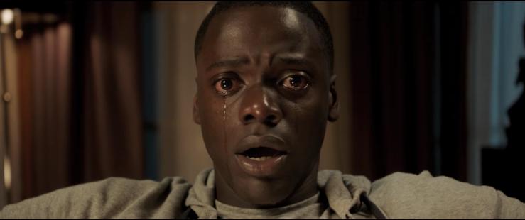 Chris Washington (Daniel Kaluuya) cries a single tear in a living room, a shocked expression on his face.