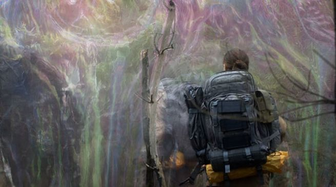 Lena (Natalie Portman) dressed in survival gear, is enveloped by a strange shimmering wall.