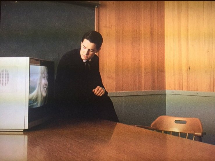 Dale Cooper (Kyle MacLachlan) sits on a wooden table. Next to him is a CRT TV, with the image of Laura Palmer (Sheryl Lee).