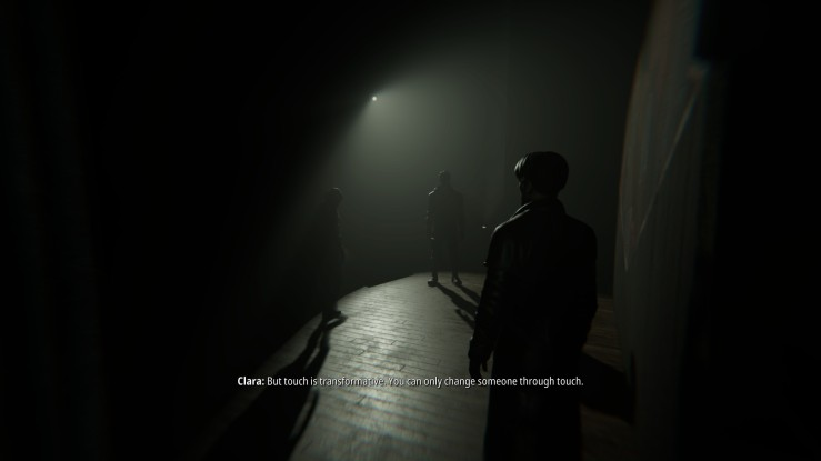 "A stage seen from the side. A single bright light illuminates the stage and three figures. They stand at points of a triangle, a fair distance from each other. Subtitles below read ""Clara: But touch is transformative. You can only change someone through touch."""